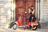 stock photo of scooter  - Young and sexy woman with her motor scooter  - JPG