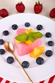 Heart shaped cake with fruits and berries on plate on napkin