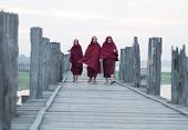 MANDALAY, MYANMAR - JAN 19, 2014: Unidentified monks from local Buddhist temple in Amarapura crossing U Bein bridge - one of most popular travel destinations in Burma.