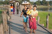 MANDALAY, MYANMAR - JAN 19, 2014: Unidentified local citizens of Amarapura crossing U Bein bridge lo