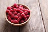 Ripe sweet raspberries in bowl on table close-up