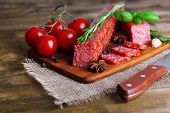 Tasty salami sausage and spices on wooden background