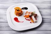 Grilled meat  with fried potato pieces and pomegranate seeds on plate, on  color wooden background