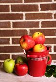 Beautiful still life with ripe sweet apples and leaves on brick wall background