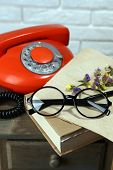 Retro phone, book and glasses on table in room