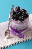 Healthy breakfast - yogurt with  blackberries and muesli served in glass jar, on color wooden backgr