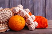 Roller brush, towel, orange and oval brushes on wooden table in front of wooden wall