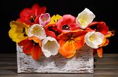 Beautiful tulips in bucket in wooden box on table on black background