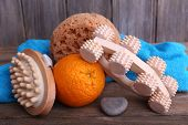 Roller brush, mop, towel, orange and oval brushes on wooden table in front of wooden wall