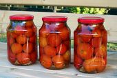 Three Glass Cans Of Red Tomatoes  On The Wooden Bench