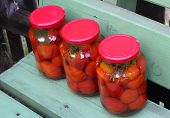 Three Glass Cans Of Red Tomatoes On The Green Wooden Bench Dagonal