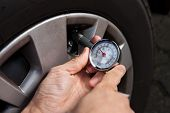 Mechanic Checking Tire Pressure Using Gauge