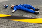 Young Unconscious Technician Lying On Street
