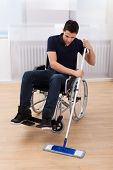 Handicapped Man Mopping Floor While Sitting On Wheelchair
