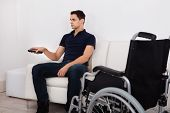 Handicap Man Using Remote Control While Watching Television