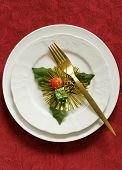 Christmas table setting (white plates on a red background)