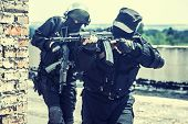 stock photo of anti-terrorism  - Two spec ops soldiers in black uniform in action - JPG