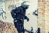 picture of anti-terrorism  - Spec ops soldier in black uniform and face mask aiming his pistol - JPG
