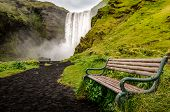 Landscape View Of Wild Skogafoss Waterfall And Bench poster