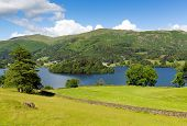 Grasmere Lake District Cumbria England UK with blue sky mountains and white clouds