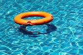Orange Life Buoy Floating On The Surface Of Blue Water