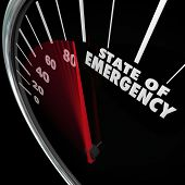 State of Emergency words on a speedometer measuring a fast approaching crisis, problem, trouble or i