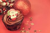 Christmas Chocolate Cupcakes With Santa Faces Against A Red Festive Background With Retro Vintage Fi