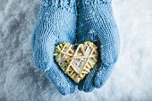Woman hands in light blue knitted mittens are holding a beautiful glossy red heart in a snow backgro