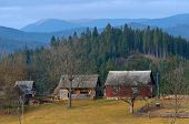 Autumn landscape with old wooden houses in the mountain village. Carpathians, Ukraine, Europe