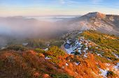 Autumn landscape in the mountains. First snow on the slopes. A small lake is covered with ice. Carpa
