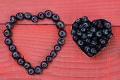 Two different heart shapes made from blueberries on a red wood background.