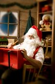 Santa Claus sitting in Rocking Chair in Workshop With Red wooden Wagon on his Lap. Vertical Composit