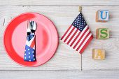 A picnic table ready for a 4th of July picnic. A red plate with fork and spoon, American Flag and bl