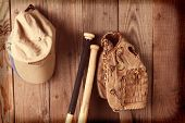 Vintage baseball equipment still life. A glove, two bats and hats against a rustic wooden wall. Horizontal format