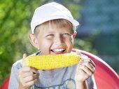 boy eating a hot summer corn
