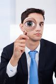 Businessman Looking Through Magnifying Glass