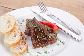 fresh hot grilled beef meat steak served with red hot pepper and white bun slices on plate over wood
