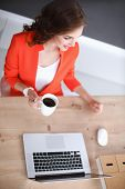 Attractive woman sitting at desk in office, working with laptop