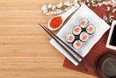 Red caviar, sushi set, sakura branch and chopsticks over bamboo table with copy space
