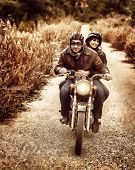 Vintage style image of two happy bikers riding on the road, active family enjoying journey on luxury