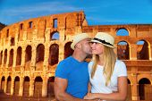 Romantic vacation to Rome, beautiful couple kissing on Colosseum background, happy traveling to Euro
