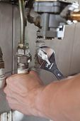 Plumber's Hands Using Wrench At Work