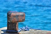 stock photo of bollard  - Old rusty mooring bollard on concrete pier with rope