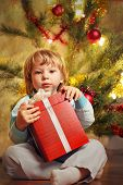happy boy with christmas gift near Christmas tree
