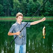 Cute boy showing fish he caught while fishing