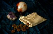 image of rune  - A plain muslin bag with wooden runes spilling out over a sparkling blue cloth with amethyst and crystal ball in the background - JPG