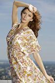 portrait of beautiful brunette girl on background blue sky