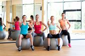 fitness, sport, training and gesture concept - group of smiling women showing thumbs up in gym