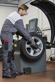 Side view of male mechanic repairing car's wheel in workshop