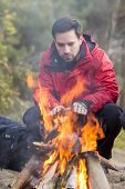Male hiker warming his hands at campfire in forest